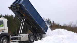 Lastbil kippar snö på snötipp.