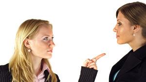 två unga kvinnliga kolleger står mot varandra, ena håller upp pekfingret mot den andra