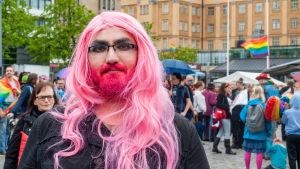 En man med rosa peruk och rosafärgat skägg ser in i kameran.