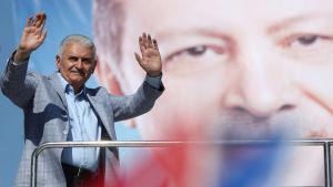 Binali Yıldırım hälsade på sina anhängare vid sitt sista valmöte i Istanbul på lördagen, med ett stort foto på Erdogan i bakgrunden.