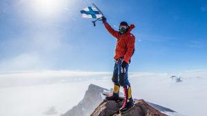 Pata Degerman heiluttaa Suomen lippua vuoren huipulla.