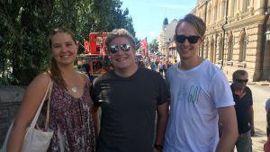 tre unga åbobor som ler i solskenet vid åstranden