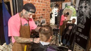 Kuvassa parturi Jouko Näivä leikkaa miehen hiuksia. Miehet heijastuvat myös peilistä.