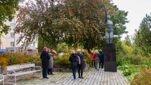 En grupp personer tittar på en staty i en stadspark.