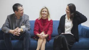 Tre personer sitter på en blå soffa inomhus. De har på sig städiga kläder. De verkar prata om någonting.