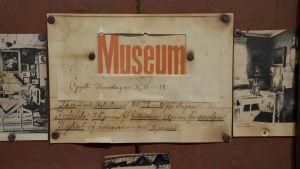 Öppetskylt för ett gammalt museum.