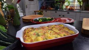 Valmis lohilaatikko ja viherkaalisalaatti pöydällä keittiössä