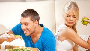 kvinna med äpple i handen tittar irriterat på glad man som äter  pizza