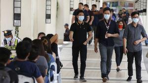 Tre män i ansiktsmasker går bredvid varandra i en folkfylld korridor.