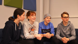 Fyra elever i högstadieåldern, två flickor till vänster och två pojkar till höger, sitter i en soffa och tittar ut ur bilden.