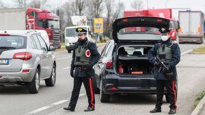 Beväpnade karabinjärer vid en av de många vägspärrarna. Den här fanns mellan provinserna Modena och Bologna på måndagen. Alla som reser mellan olika orter måste nu redovisa för sina skäl till resan .