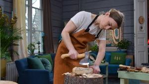 Den svenska yxmakaren Julia Kalthoff hugger till ett yxskaft med en täljyxa.