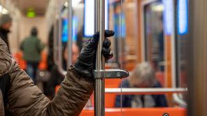En hand håller i ett räcke i metron.
