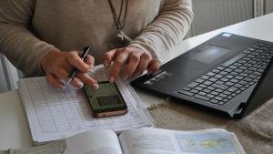 Ela Strandberg knäpper på sin telefon på bordet.