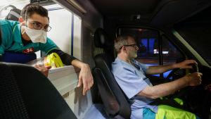 Två vårdare i en ambulans som kör genom ett nattligt Bryssel.