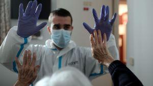 Fysioterapeut i blå plasthandskar och äldre patient sträcker upp sina händer till möte, på äldreboende i Spanien