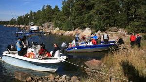 Två båtar vid land som är fullproppade med människor i båtarna. Det är en solig sommardag.