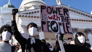 Tre stycken demonstranter som bär ansiktsmask.