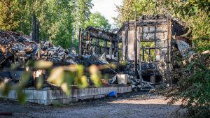 Brandhärjat hus i sommargrön miljö