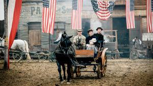 Hevosvankkurit 1900-luvun alun Amerikassa, kyydissä 3 ihmistä. Kuvassa näkyy Yhdysvaltain lippuja.