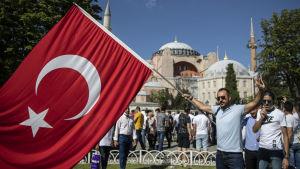 Man med turkiets flagga står utanför Hagia Sofia. I bakgrunden står flera människor.