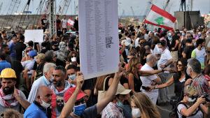 Demonstration och minnesstund i Beiruts hamn. En libanesisk demonstarant bär en skylt med namnen på de personer som dog efter explosionen i Beirut 4 augusti 2020.