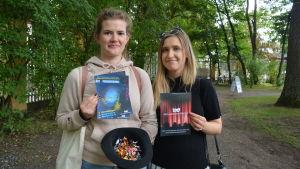 Mecki Ruokolahti och Nelli Salonen håller i teaterbroschyrer.