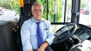 En man som sitter vid bussratten.