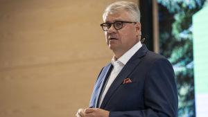 UPM:s vd Jussi Pesonen fotograferad från sidan i halvbild. Han har en blå kostym på sig och händerna framför magen.