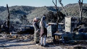 Migranter tittar på spåren efter branden i lägret Moria