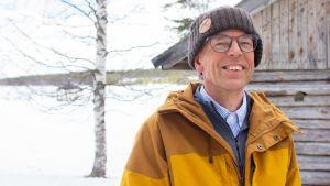Avaruusfyysikko Esa Turunen keltaisessa ulkoilutakissaan, harmaan vajan edessä. Taustalla näkyy jäinen joki.