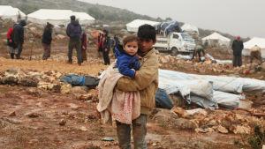 Bild på äldre barn som håller yngre barn i famnen. I bakgrunden syns flyktingläger under konstruktion.
