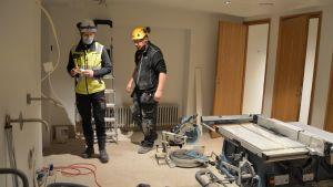 Två byggarbetare vi en källarvåning.