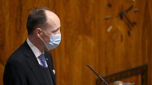 Jussi Halla-Aho i riksdagssalen. Han bär munskydd.