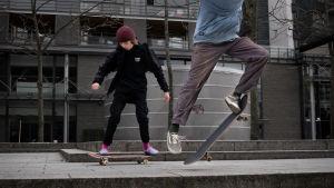 Två ungdomar åker skateboard i Kampen i Helsingfors