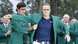 Jordan Spieth klär på sig den gröna kavajen som vinnare av US Masters 2015.