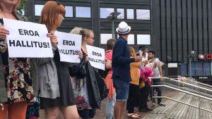 Demonstranterna står med skyltar som kräver regeringens avgång.