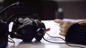 Hörlurar på en pulpet inför hörförståelseprov.