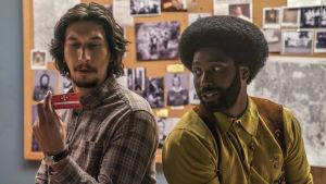 Flip (Adam Driver) och Ron (John David Washington) sitter tillsammans och ser på medlemskortet till Ku Klux Klan.