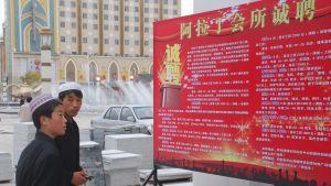 Kommunistpartiet fäster propagandaplanscher utanför moskéerna. Muslimerna uppmanas bland annat att älska partiet.