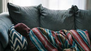Ihminen makaa sohvalla.