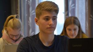 Axel sitter i klassrummet med sin dator framför sig. Han är koncentrerad.