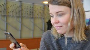 Anna-Emilie Lindberg med mobiltelefon.