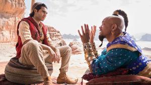 Aladdin (Mena Massoud) lyssnar då anden i flaskan (Will Smith) talar.