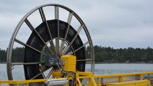 Ett stort hjul med vajer på gula Högsarfärjan.