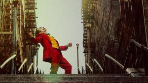 Joker (Joaquin Phoenix) iklädd clownmask och röd kostym står uppe på en trappa och dansar.