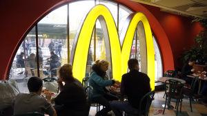 Restauranggäster på McDonalds, i bakgrunden kedjans kännspaka gula M.