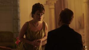 En festklädd kvinna i en dunkel salong lutar sig fram mot en sittande man.
