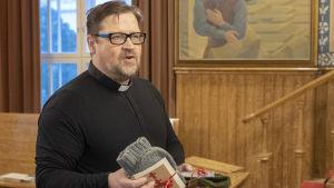 Präst med julklappar i handen.