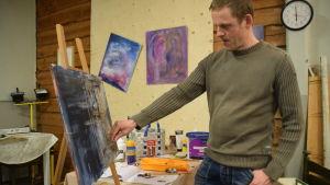 Niclas Skog målar en tavla.
